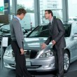 Car salesperson explaining car features to customer — Stock Photo #3814907