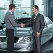 Car salesperson shaking hands with customer at showroom — ストック写真