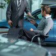 Car salesperson giving catalog to businessman — Foto Stock