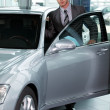 Stock Photo: Portrait of car salesperson getting in car at showroom