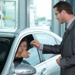 Man getting keys to new car through salesperson - Stock Photo