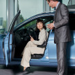 Car salesperson explaining car features to customer — Foto de Stock