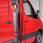 Young man peeking through van door — Stock Photo