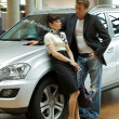 Young man conversing with woman in car showroom — Stock Photo