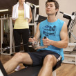 A young man exercising with a personal trainer - Stockfoto