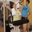 A young woman exercising with a personal trainer - Stock Photo
