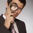 Young caucasian businessman with magnifying glass — Stock Photo