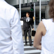 Young caucasian businessman in park walking on green light on zebra - Stock Photo