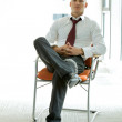 Young confident caucasian businessman sitting on office chair — Stock Photo #3818178