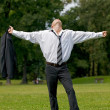 Stock Photo: Businessman standing in park with arms outstretched