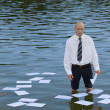 Royalty-Free Stock Photo: Portrait of businessman standing in lake with papers floating on water