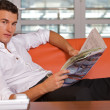 Young man reading newspaper, portrait — Stock Photo