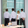 Royalty-Free Stock Photo: Business team looking through window at office