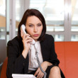 Businesswoman conversing on landline phone, portrait - Stock Photo