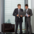Businessmen looking at laptop in office — Stock Photo
