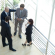 Stock Photo: Businessmen and womstanding together by railing conversing