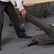 Businessmen pulling colleague's leg at office — Stock Photo