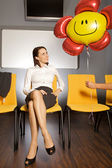 Businesswoman looking at balloon in waiting room — Stock Photo
