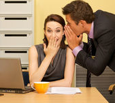 Businessman whispering in businesswoman's ear at office — Zdjęcie stockowe