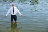 Businessman standing in lake, eyes closed — Stock Photo