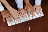 Human hands on computer keyboard, elevated view — Stock Photo