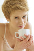 Woman drinking caffee in bed — Stock Photo