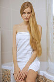Young woman wearing a towel in bathroom — Stok fotoğraf