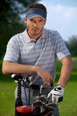 Portret młodego człowieka stojącego przez torby golfowej pełne laski — Zdjęcie stockowe