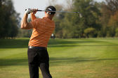 Young man swinging golf club, rear view — Stock Photo