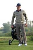Jeune homme transportant chariot avec sac de golf — Photo