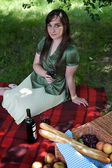Elevated view of young woman holding wineglass, sitting in park — Stock Photo