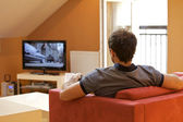 Rear view of young man watching television — Stock Photo