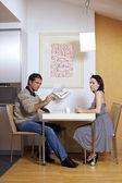 Porträtt av kvinna som sitter på frukostbordet medan man läser tidningen — Stockfoto