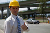 Portrait of architect in hardhat showing thumbs up sign at construction sit — Stock Photo