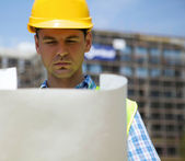 Engineer looking at blueprint on construction site — Stockfoto