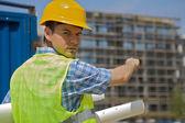 Portrait of engineer holding blueprint on construction site — Stock Photo