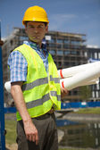 Portrait of engineer holding blueprint at construction site — Stockfoto