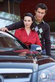 Porträtt av ungt par stående med ny bil — Stockfoto