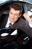 Angry young man clenching his fist, sitting in new car — Stock Photo
