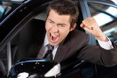 Angry young man clenching his fist, sitting in new car and shouting — Stock Photo