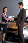 Car salesman standing with female customer by new car in showroom, shaking — Stock Photo