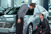 Car salesperson explaining car features to customer — Stock Photo