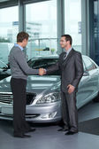 Car salesperson shaking hands with customer at showroom — Stock Photo