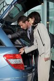 Vendedor de carro mostrando características do carro para o cliente — Foto Stock