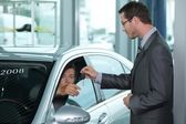 Man getting keys to new car through salesperson — Stock Photo