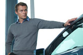 Young man standing by new car — Stock Photo