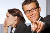 Portrait of businessman pointing while businesswoman using mobile phone — Stock Photo