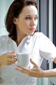Young woman drinking coffee in the morning — Stock Photo