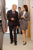 Business team walking thru corridor and talking — Stock Photo