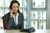 Portrait of young confident caucasian businesswoman talking on phone — Stock Photo
